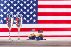 American flag, two glasses of champagne and cupcakes. American flag, two glasses of champagne and cute cupcakes Royalty Free Stock Photo