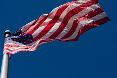 American Flag Unfurls In Interesting Pattern On Flagpole Royalty Free Stock Image