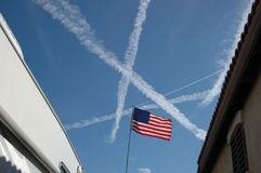 American flag and vapor trails. An american flag flies with multiple airplane vapor trails in the background Stock Photo