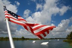 American Flag Wakeboard Ramps. An American flag waves and flutters patriotically in the morning breeze with wakeboard ramps in the background on the ski rixen Royalty Free Stock Image
