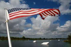 American Flag Wakeboard Ramps. An American flag waves and flutters patriotically in the morning breeze with wakeboard ramps in the background on the ski rixen Stock Image