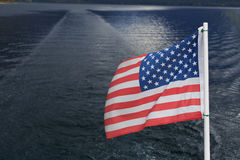 American Flag Water Background. The American Flag flies behind a boat on Lake McDonald in Glacier National Park, Montana Stock Photo