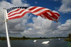 American Flag Wakeboard Ramps. An American flag waves and flutters patriotically in the morning breeze with wakeboard ramps in the background on the ski rixen Royalty Free Stock Photography