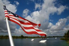 American Flag Wakeboard Ramps. An American flag waves and flutters patriotically in the morning breeze with wakeboard ramps in the background on the ski rixen Royalty Free Stock Photo