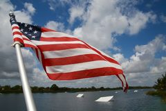 American Flag Wakeboard Ramps. An American flag waves and flutters patriotically in the morning breeze with wakeboard ramps in the background on the ski rixen Stock Images