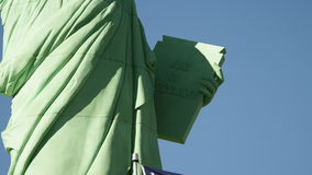 American flag waves in the foreground of statue of liberty stock footage