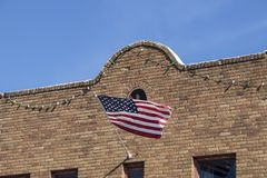 American flag waves from retro southwestern style brick building facade hung with party lights.  stock image
