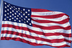 American flag waving. American flag blowing in the wind with a blue sky Royalty Free Stock Image