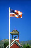 American flag waving above one room schoolhouse,. Wellington, NV Royalty Free Stock Images