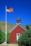 American flag waving above one room schoolhouse, Stock Photos