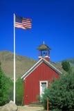 American flag waving above one room schoolhouse,. Wellington, NV Stock Photos