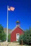American flag waving above one room schoolhouse,. Wellington, NV Royalty Free Stock Image