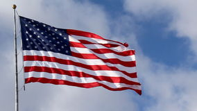 American Flag Waving against Blue Sky. And white clouds. Filmed at 60 fps and slowed down to 30 fps stock video footage