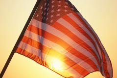 American Flag waving against sunny background. American flag with sun shining through the stripes Stock Images