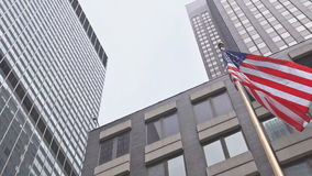 American flag waving against two skyscrapers and a blue sky. An American flag waving against two skyscrapers and a blue sky stock footage