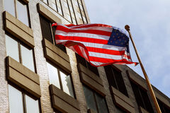 American flag waving against two skyscrapers and a blue sky. Stock Photos