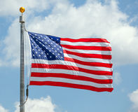 The American flag waving on blue sky. The American flag waving against a blue sky on a flag pole, focus on star of waving flag royalty free stock images