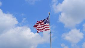 American Flag waving on blue sky background. USA flag stock video footage