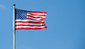 American flag waving with clear blue sky. Background in strong wind in USA, focus on star of waving flag Stock Photography