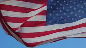 American flag waving. Close-up of an American flag flying in the wind against a background of clear sky. American Flag Waving. Close up of American flag waving stock footage