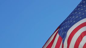American Flag Waving. Copy paste on a blue sky background. USA flag flaping in wind. Close-up of an American flag flying in the wind against a background of stock video footage