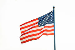 American flag waving on flagpole. Isolated white background royalty free stock image