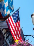 American Flag Waving Proudly. American Flag Hanging from the Side of Storefront Royalty Free Stock Image
