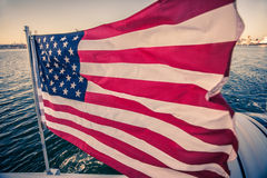 American flag waving on a rapid moving boat. The closeup view of the USA flag waving on a rapid moving vessel in the bay Royalty Free Stock Photography