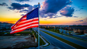 American Flag waving at Sunset illuminated by Golden Hour Sun rays above Suburbs Aerial drone view stock image