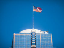 American flag waving on top of a modern skyscraper Stock Photography