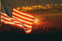 The American flag waving in View of Manhattan New York City sunset on the background. The American flag waving in sunset on the background of New York Manhattan stock photos