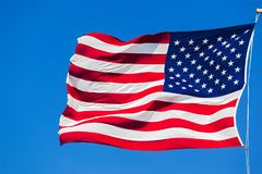 American flag on the blue sky. American flag waving in the wind against the blue sky Royalty Free Stock Photo