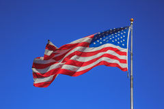 American flag waving on the wind on blue sky background Royalty Free Stock Photos