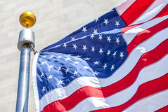 American flag waving in the wind. Close-up American flag waving in the wind with flag pole, focus on star of waving flag Royalty Free Stock Photo