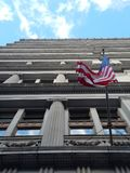 American flag waving on a windy day, view looking straight up from directly below, in front of historic office building facade stock photography