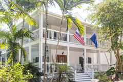 American Flag on White Wood House with Two Verandas Stock Images