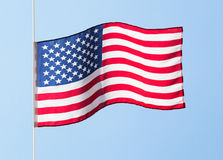 American flag in the wind against a blue sky Royalty Free Stock Photo