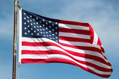 American Flag On Windy Day. An American flag blowing in the wind on a bright sunny day Stock Photography