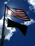 American Flag on Windy Day Sunlight Blue Sky and Clouds Stock Image
