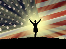 American flag. A woman celebrating her freedom with US American flag in the backdrop Stock Photo