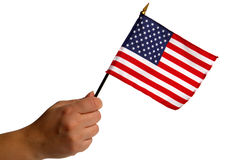 American Flag in Woman Hand Isolated on White. Woman hand holding a small patriotic American US flag isolated on white Stock Image