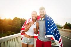 American flag - woman and man USA sport athlete winner cheering waving US flag Stock Photography
