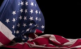 American flagged draped over itself with a black background. Patriotic American flag beautifully draped over itself in front of a black background with soft stock image