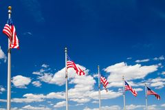 American flags. Series of American flags flying in the wind over blue sky with white clouds Royalty Free Stock Photo