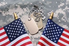 American Flags and Dog Tags. Closeup of two crossed American Flags on camouflage material with dog tags in the middle. The ID tags are blank. Horizontal format Royalty Free Stock Photos