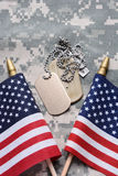 American Flags and Dog Tags. Closeup of two crossed American Flags on camouflage material with dog tags in the middle. The ID tags are blank. Vertical format Royalty Free Stock Photos