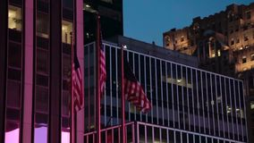 American Flags in the evening in New York. America Flags waving in the wind against a background of building in the evening in New York. Evening shot of the stock footage