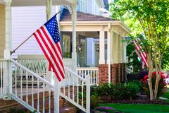American Flags on Front Porches. A line of suburban homes display large American Flags royalty free stock image