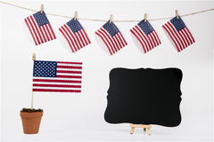 American flags hanging on clothesline on white background. American flags hanging on clothesline isolated on white background with message board royalty free stock photo