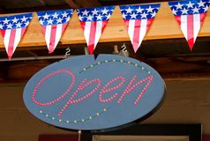 American flags and open sign. Close up of open sign with decorative American flag bunting Royalty Free Stock Photo